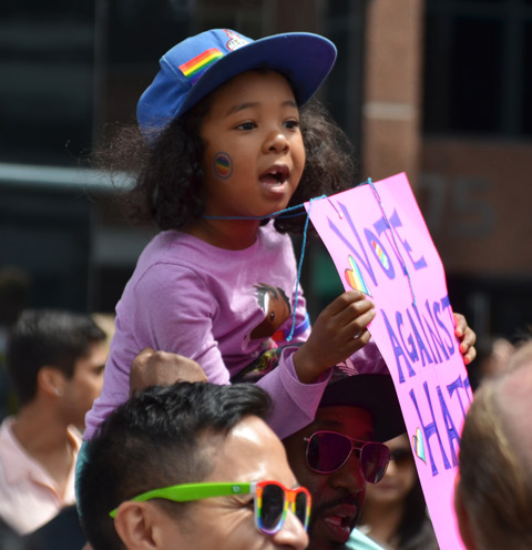 a young black girl is sitting on her father's shoulders. She is holding a pink sign with purple hand written letters that say vote against hate