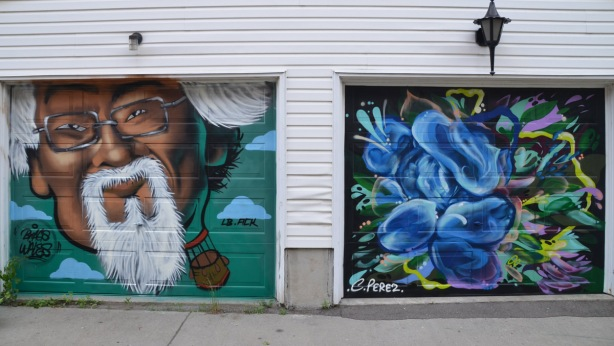 a mural on a garage door in an alley, part of butterflyways project - two adjacent garage doors, the left one is painted by braes and is a portrait of David Suzuki. On the right is a blue mural by C. Perez