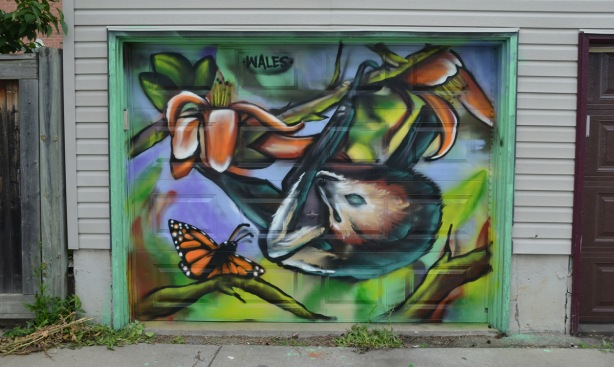 a mural on a garage door in an alley, part of butterflyways project - a possum and a butterfly by wales
