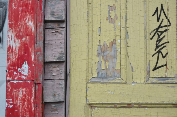 yellow wood door with peeling paint, red gate, also with peeling paint, up close of parts of them