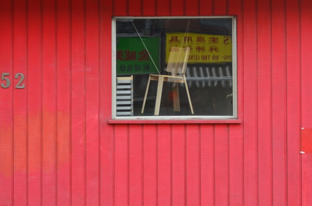 bright red wall with window. A chair is in the window, also reflections of chinese signs, number 52 on the wall