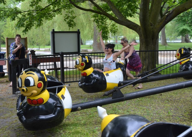 a young woman site in a child's amusement park ride where the seats are the shape of bumblebees. her hands are in the air. Another woman is pushing the bee to make it go around like it would if the ride were were operating