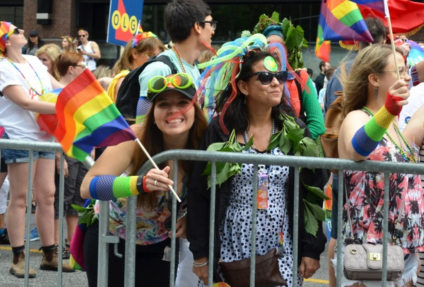 woemn smiling for the camera, dressed up in colourful clothes and holding rainbow flags.