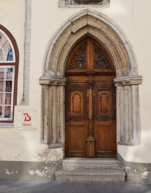 old carved wooden door with stone gothic arch around it. Now a restaurant in Tallinn, Bordoo restaurant
