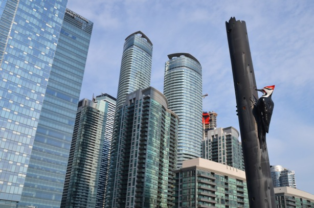 large sculpture of a woodpecker on a pole in the foreground, many glass skyscrapers condos in the background
