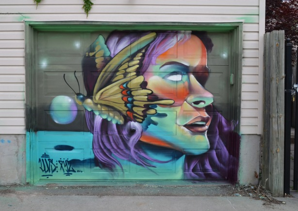 a mural on a garage door in an alley, part of butterflyways project - a person's face in profile, with a butterfly spread over the back part of the head