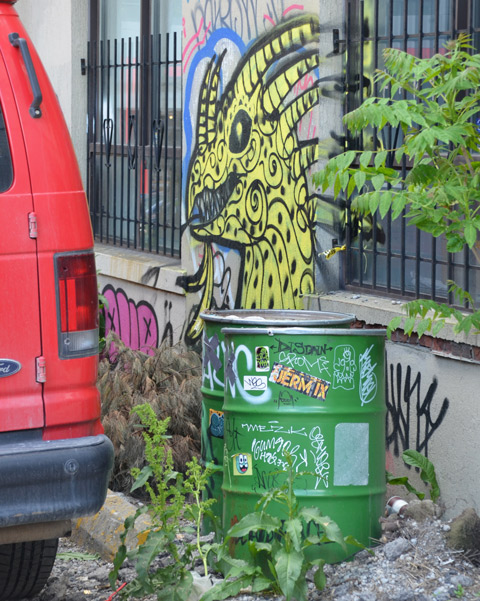 behind a red van and two green metal barrels, a yellow monster street art painting on a wall