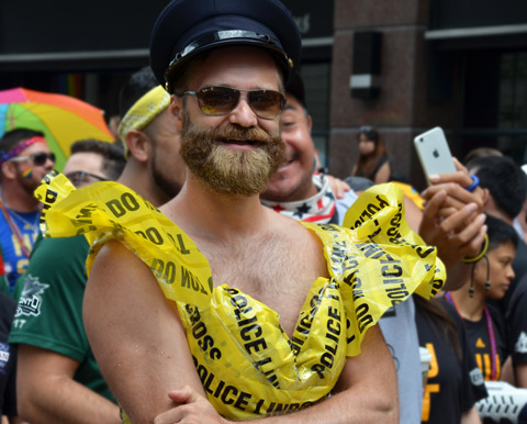 man with bushy beard, a black cap and a top made out of yellow police caution tape