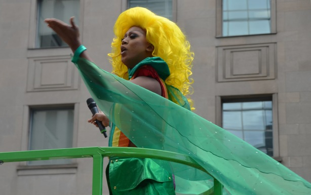 up on the TD float in the pride parade, a person is a long wavy yellow wig and wearing a striped top and short green shiny skirt, is blowing kisses to the crowd.