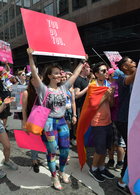 a woman wearing a t shirt that says free hugs is carrying a pink sign that says you do you
