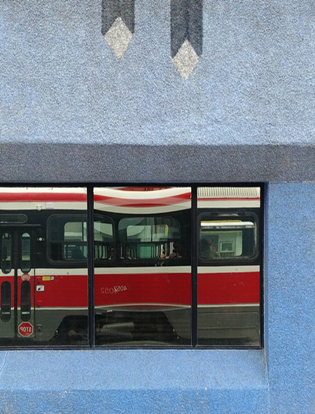 reflections of a TTC streetcar in the window of a pale blue building.