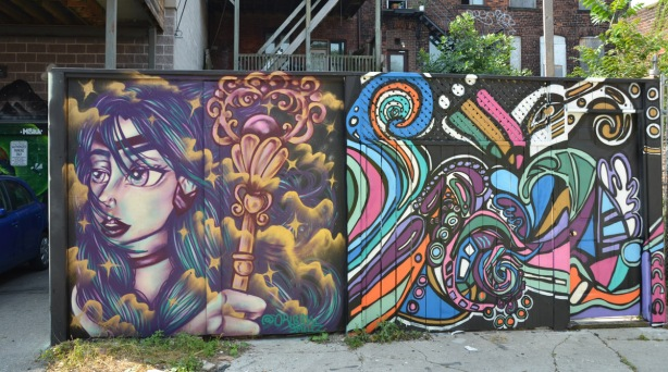 2 square street art paintings on an alley fence, one is a woman with a wand-like object in her hand and the other is swirls of colours