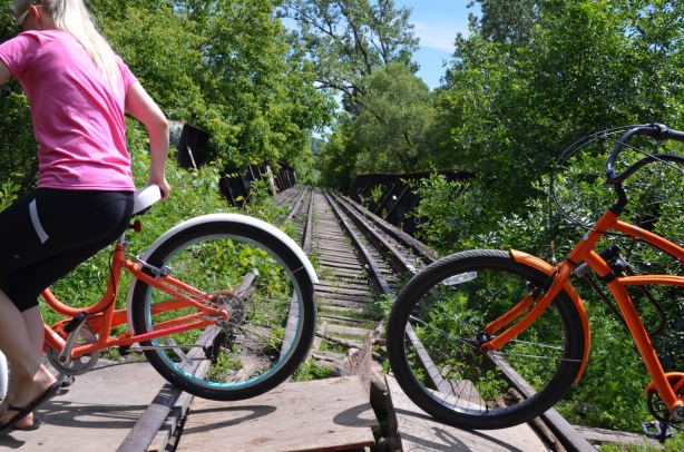 two cyclists walk their bikes across loose pieces of plywood over unused railway tracks