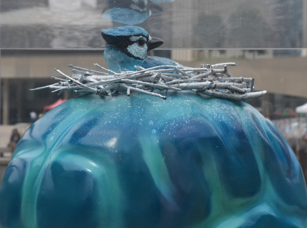 close up of part oa brain sculpture, the brain is painted blue and teal and there is a blue jay sitting on a nest on top of the egg (the bird is part of the sculpture)