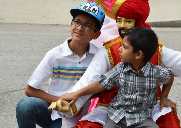 two young boyus pose with a manniquin dressed in traditional Indian (South Asian) costume
