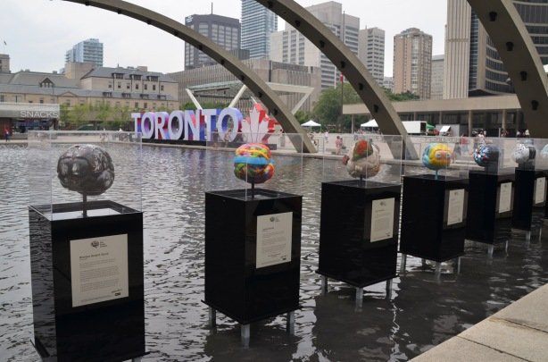 a line of sculptures on display, podius standing in the water of the fountain, arches, and 3D Toronto sign in the backgruond.