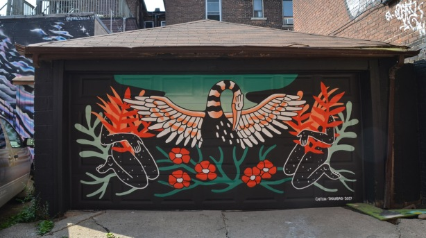 mural on a garage door in orange, black, white and green of a bird with wings spread, standing on flowers, with a woman kneeling behind each wing