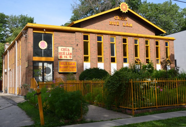 brick building with yellow trim, yellow fence around it, sign says Chua Hue Lam Buddhist Church