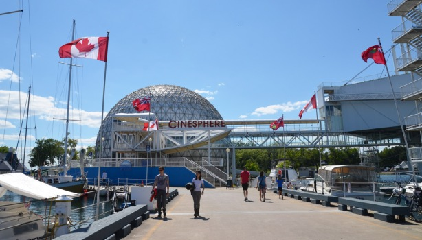 flags line the walkway leading from the dome shaped cinesphere at Ontario Place,