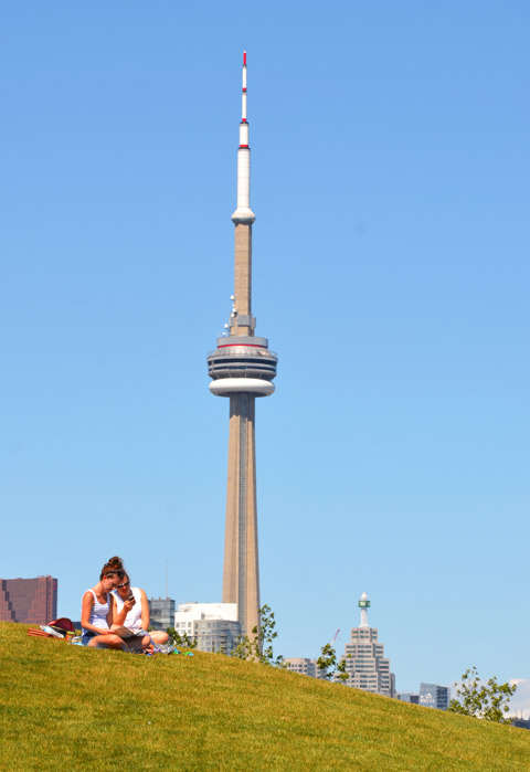 couple, man and woman, sitting together, on a grassy hill. The CN Tower is behind them.