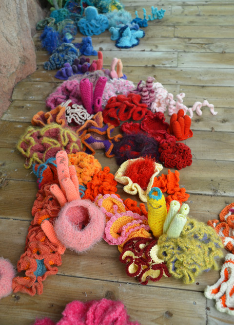 crocheted sea creatures clinging to the underside of a wood bridge