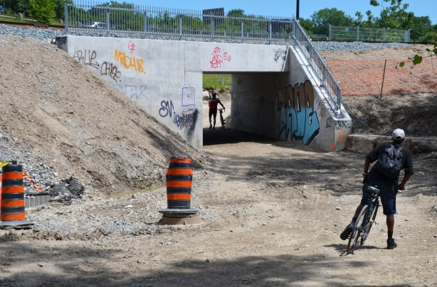 a cyclist walks his bike over a gravel travel under a bridge that has just been renovated, another bike rider is dismounting