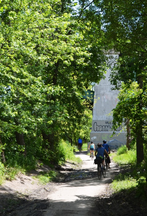cyclists on a path through the trees, a bridge support is beside the path