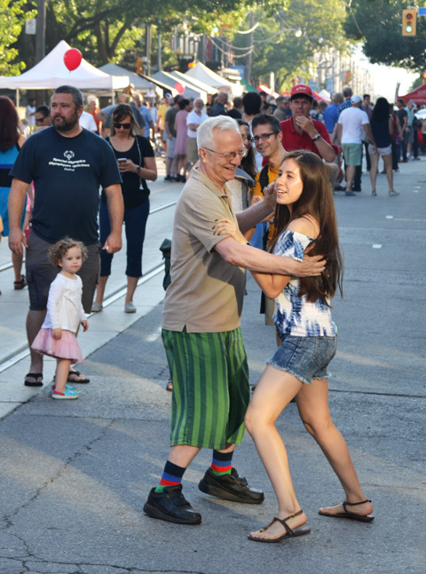 a couple dances on the street, attending a music street festival, some people look on.