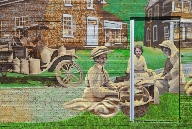 a maural painted on a wall and door, historic scene, women in period costume (early 1900s?) sitting on the grass with some baskets, old fashioned car behind them.