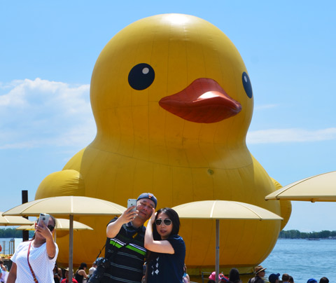 three people are taking selfies in front of the big yellow duck