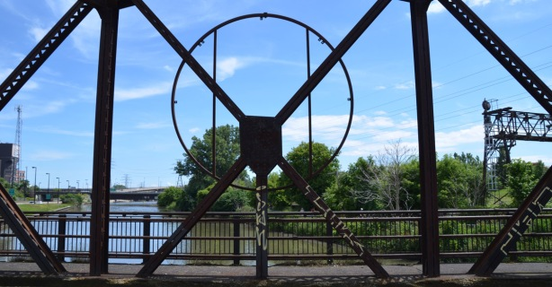 metal work of the side of a bridge frames the view of a river and trees and city buildings, Don River, abandoned bridge