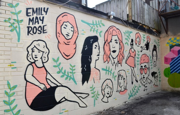 mural by emily may rose of various women's faces, in black and white and pink, long black hair, pink head scarf, pink dress, short hair,