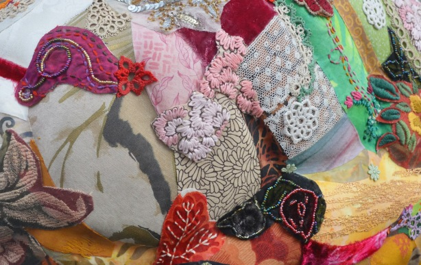 close up of a fabric collage on a sculpture, bits of fabric with flowers on it, some embroidered leaves and flowers, lace and trim too,