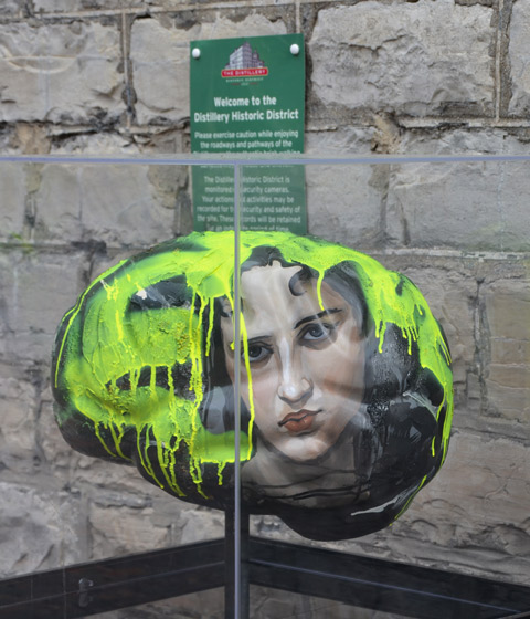 outdoor display in a clear acrylic box, a sculpture in the shape of a brain, with the picture of a woman's face on the side, yellow paint drips down from the top of the brain.
