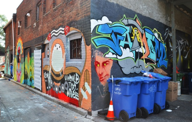 corner of a building in a lane showing the street art on two sides