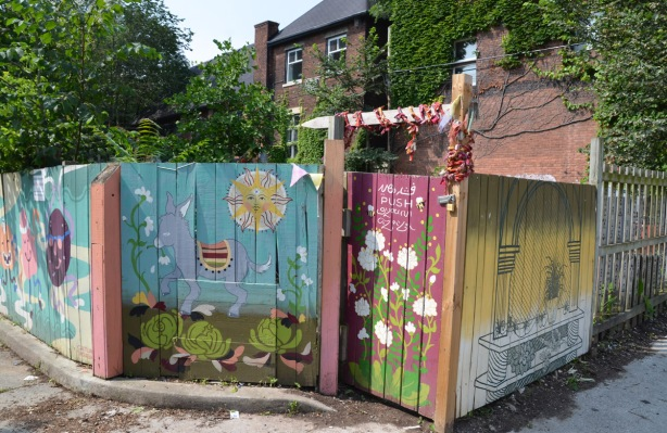 wooden fence around a backyard that has been painted with garden scenes, cabbages, flowers, sun, and a donkey