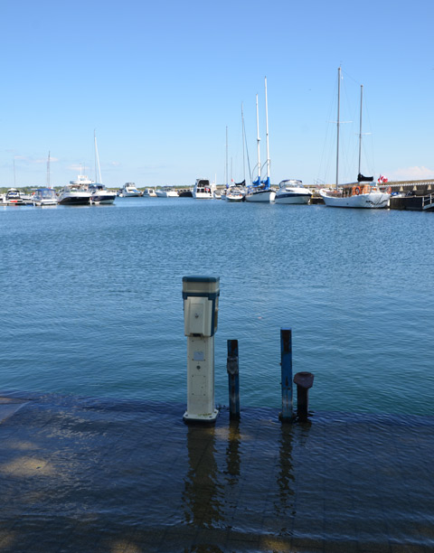 an electrical plug in station stands in the water by a flooded dock at Brigantine Cove, Ontario Place, with sailboats in the background.