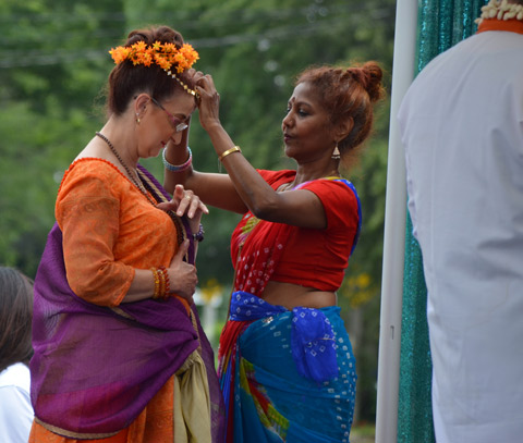 one woman adjusts the floral headband on another woman, both are dressed in traditional South Asian clothing
