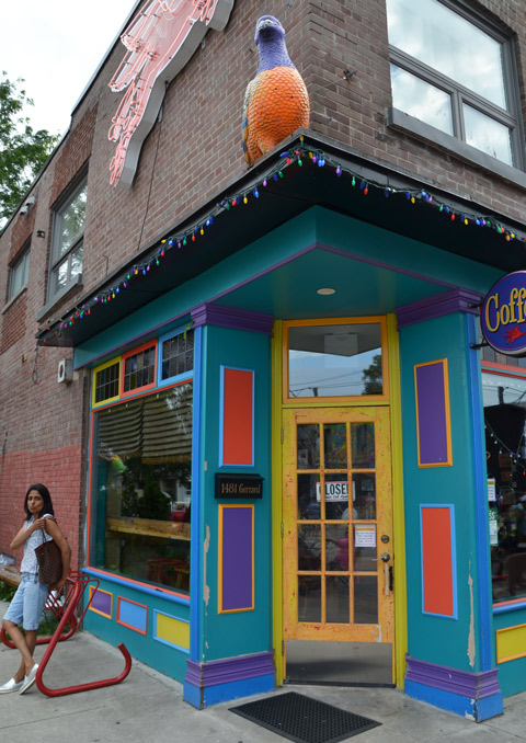 front entrance of the Flying Pony coffee shop, bright blue door frame, yellow door, orange and purple squares on the door frame