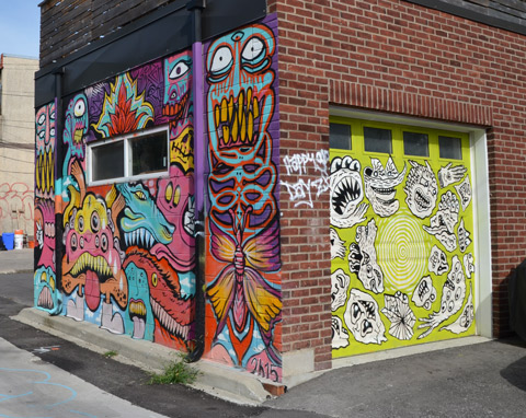 street art on a garage door, bright yellowish green with black and white faces