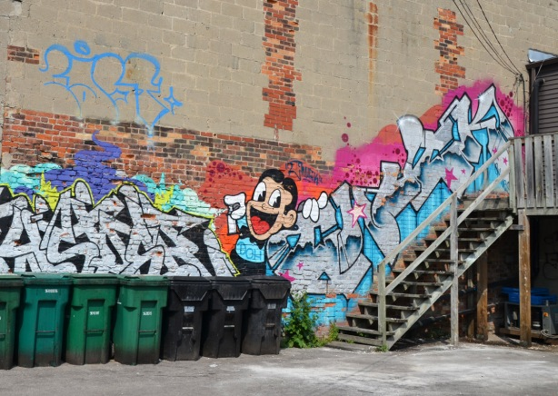 a line of black and green rubbish garbage bins along a wall that has street art on it, picture of a boy with a spray paint can in his hand along with some text , stairs leading up to the upper level of the building as well