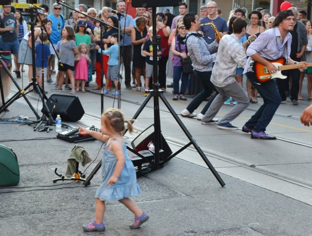 a little girl runs towards a temporary stage set up on the sidewalk, she is pointing to it. The musicians have moved forward and are playing closer to the crowd