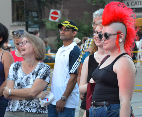 people, part of a larger crowd watching a street performance, one woman has a bright orange mohawk hairdo.