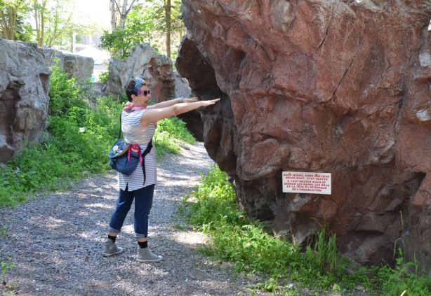 a woman standing between two rocks pretends to be riding in a boat as she points to a sign that says