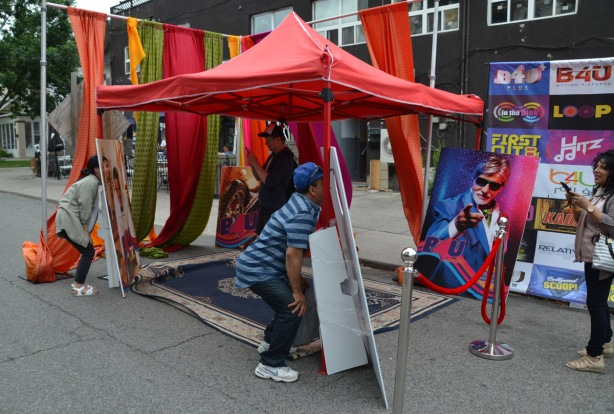 at a street festival, two people are putting their heads through cut outs while others take their picture, cut outs are on faces of Bollywood actors and actresses.