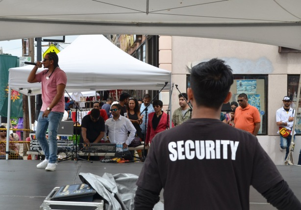 a man with a black shirt with the word security on the back watches a performance of a rap artist who is on a stage with many people watching him