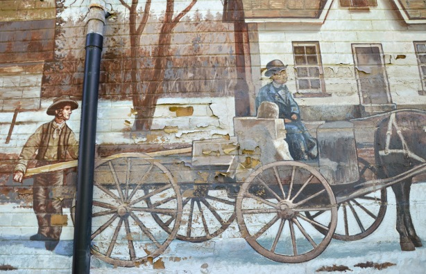 part of a mural, horse drawn wagon, one man sitting at the front of the wagon, another man standing at the rear loading the wagon with lumber