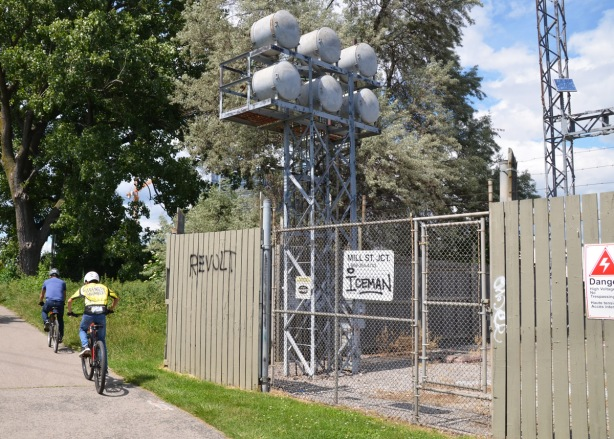 two boys ride bikes past the Mill Street Junction hydro station, fenced in area with danger signs,