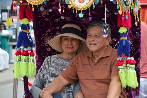 an older couple pose for a picture while they are sitting in a decorated cart, purple velvet, and many colourful tassles