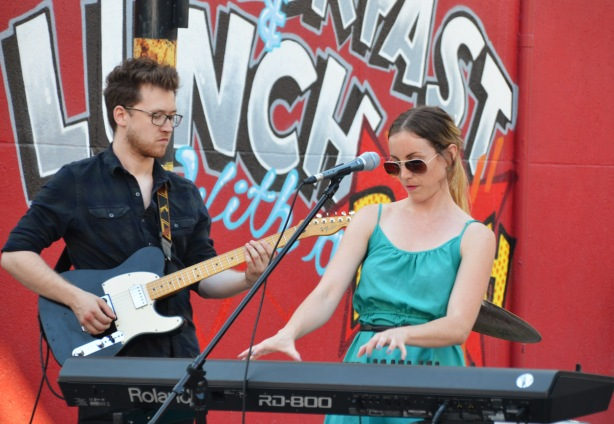 a woman in sunglasses and teal dress plays the keyboards. A man with a small beard is playing the guitar beside her, a red wall with text street art is behind them.